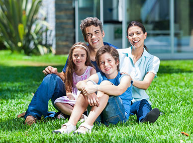A happy family sits on their lawn