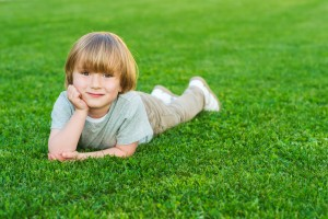 A young boy laying in a field of lush green turfgrass