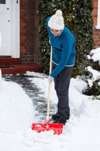 15439788 - person shovelling snow off driveway outside her house